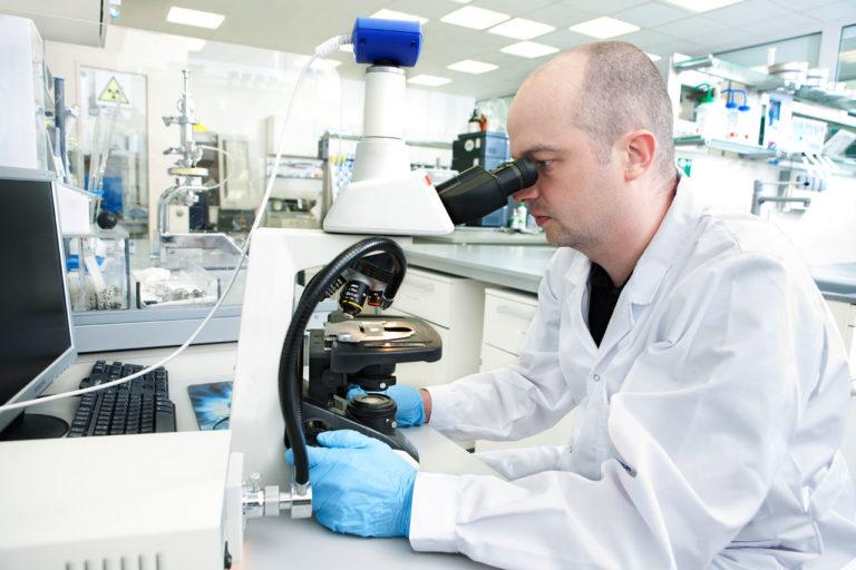 Laboratorium Działu Preformulacji - badanie morfologii kryształów, laborant patrzący przez mikroskop