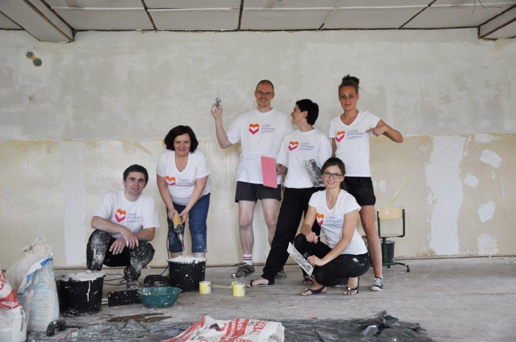 Grupa wolontariuszy w odnowionym budynku