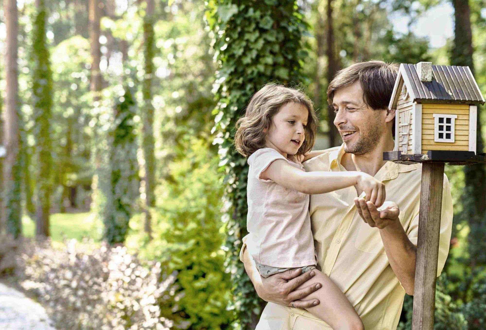 Mężczyzna trzymający na rękach dziewczynkę która nasypuje ziarna do karmnika