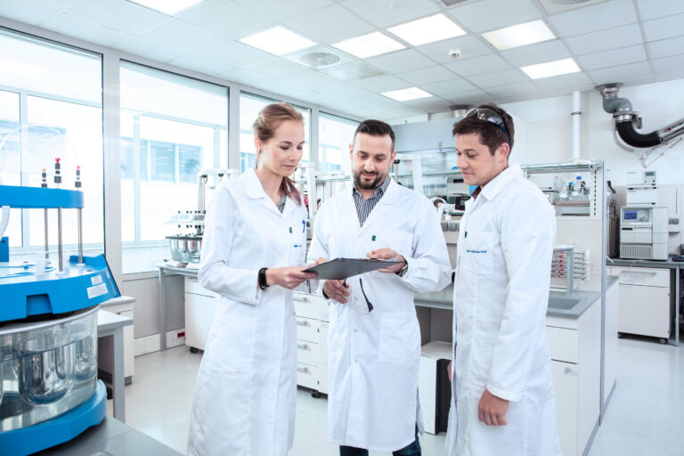 Three people in laboratory looking at document