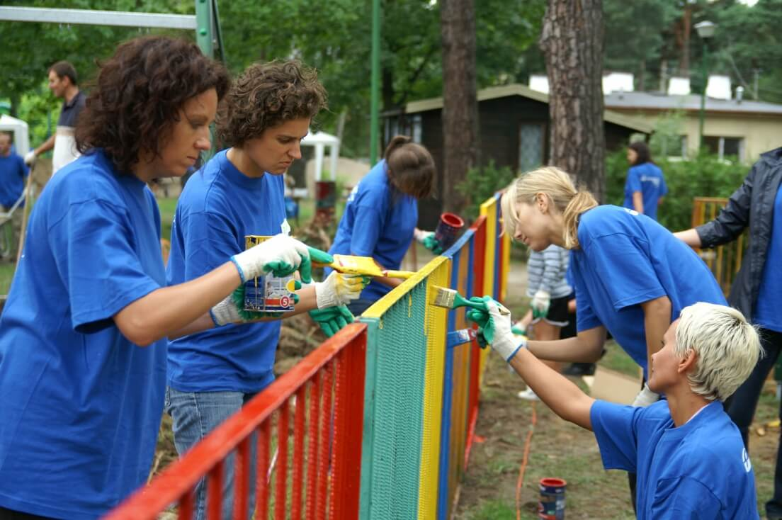 Women in blue T-shirts paint the fence in different colors