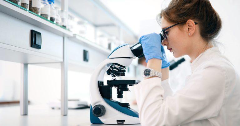 Kobieta patrząca przez mikroskop