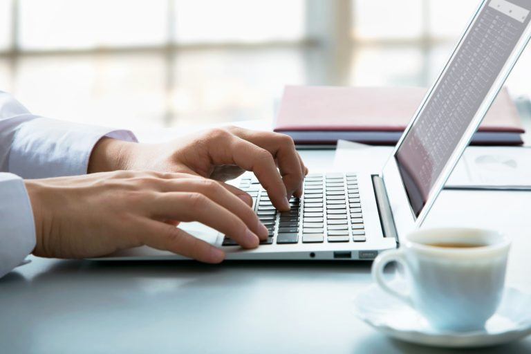 Dwie dłonie na klawiaturze laptopa