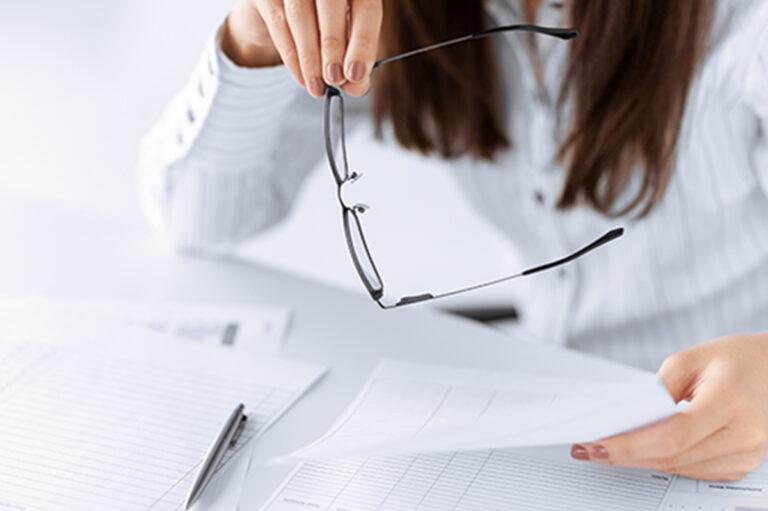Kobieta trzymająca okulary i kartkę papieru