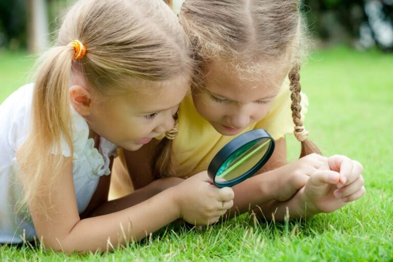Two little girls looking at the grass through a magnifying glass