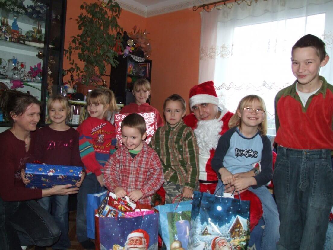 Wolontariusz przebrany za świętego Mikołaja w otoczeniu dzieci